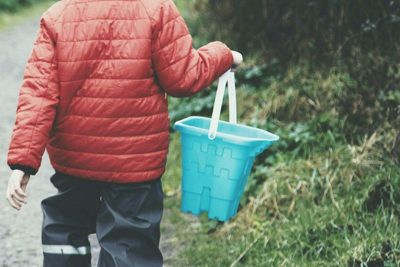 Midsection of boy holding bucket