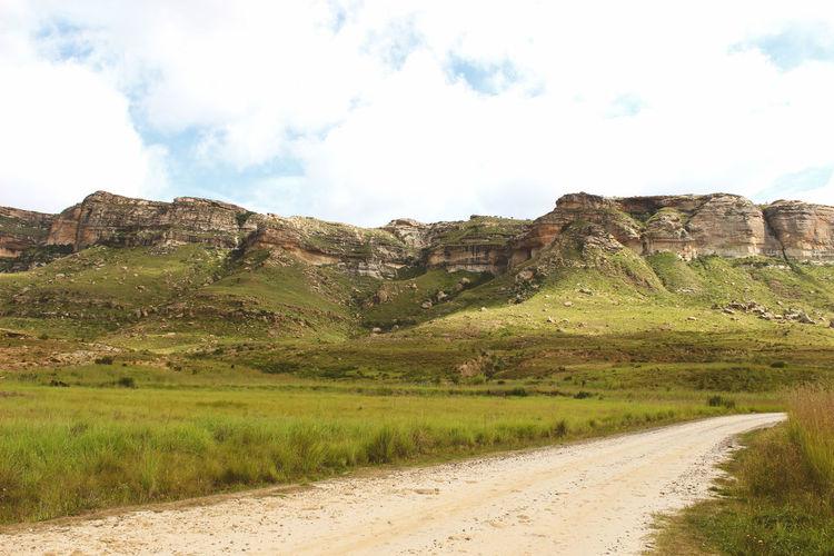 Dirt road amidst landscape against sky