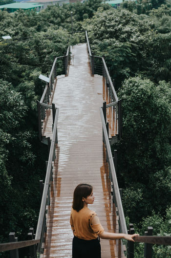High angle view of woman walking on footbridge by trees