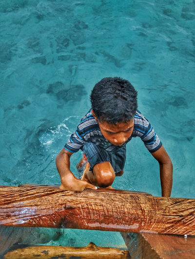 High angle view of boy holding swimming pool
