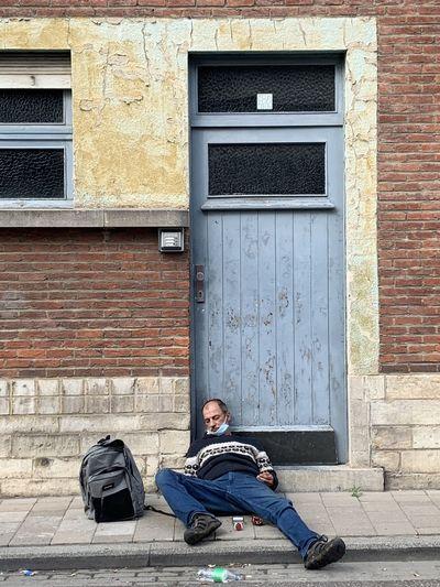 Full length of man sitting against brick wall