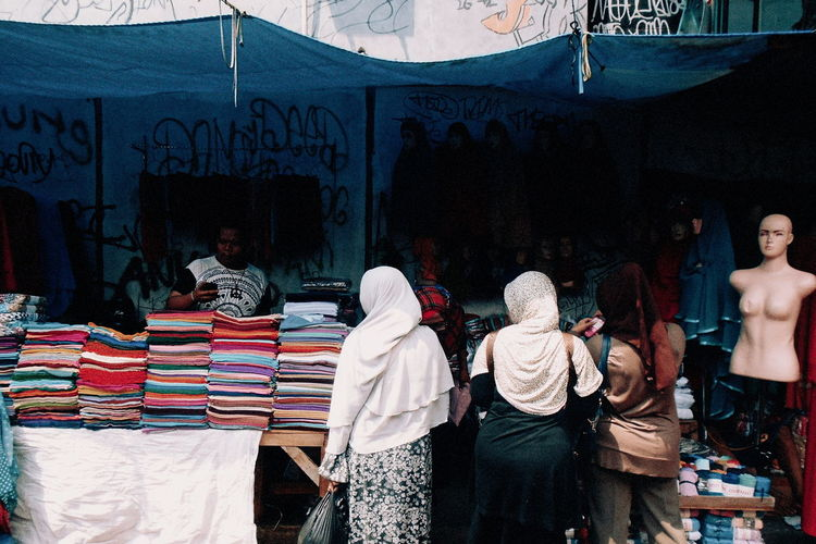 Rear View Of Woman In Hijab Standing By Clothes At Market Stall