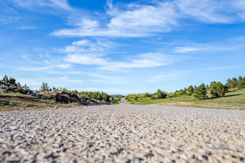 Beauty In Nature Cloud - Sky Day Direction Gravel Nature No People Outdoors Plant Road Rock Scenics - Nature Selective Focus Sky Solid Street Surface Level The Way Forward Tranquility Transportation Tree