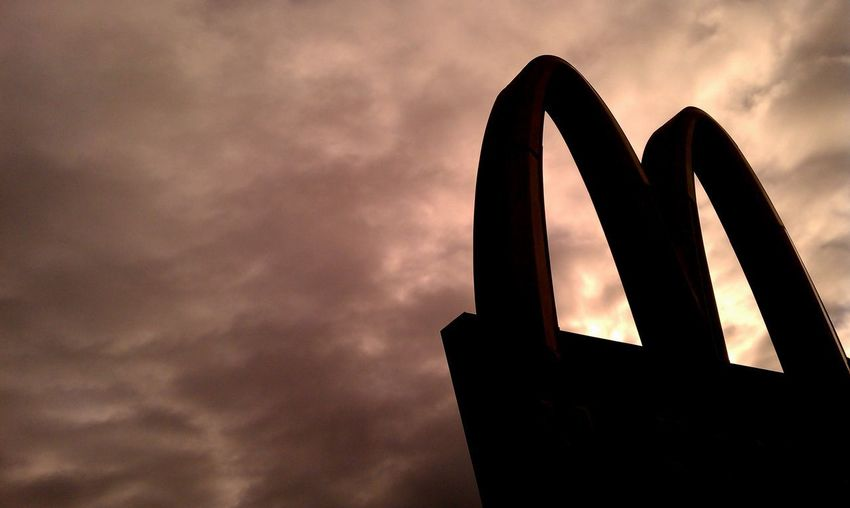 McDonalds sign silhouetted with moody clouds above Business Diet Economy Franchise M McDonald McDonald's Calories Close-up Cloud - Sky Food Desert Healthcare Food Junk Food Low Angle View Mcd Mcdonalds No People Overweight Silhouette Sky Sodas Storm Cloud Weather Weight Weight Gain