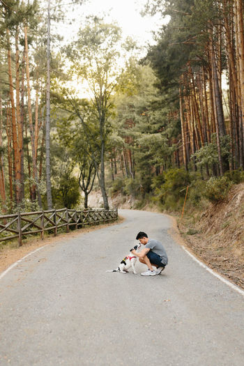 Man sitting on road in forest