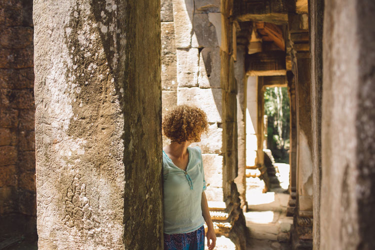 Siem Reap Cambodia Angkor Curly Hair Girl One Person Architecture Casual Clothing Built Structure Real People Standing Day Women Adult Lifestyles Hairstyle Rear View Leisure Activity Architectural Column Building Three Quarter Length Building Exterior The Past Outdoors