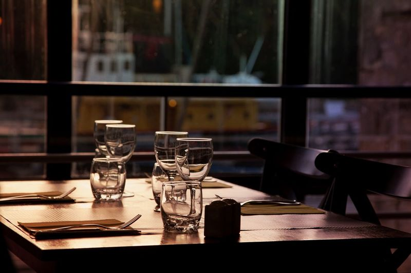 Empty restaurant with the port view Table Indoors  Restaurant Focus On Foreground No People Chair Drinking Glass Food And Drink Pepper Shaker Food And Drink Industry Close-up Day Bar Cafe Empty Empty Places