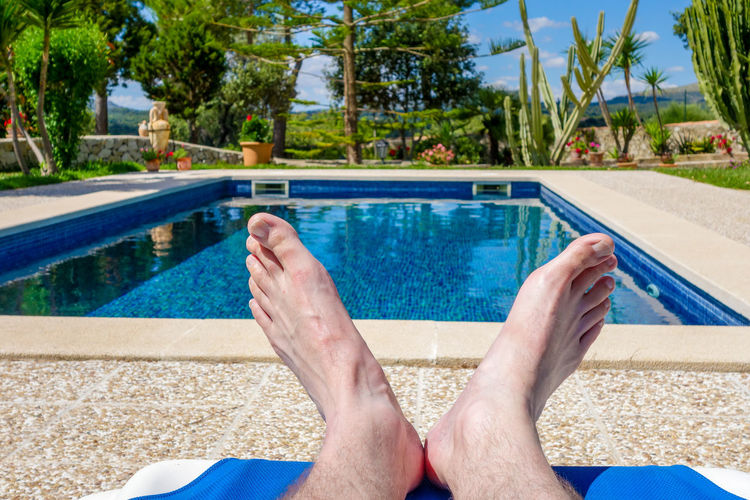 Low section of man relaxing in swimming pool