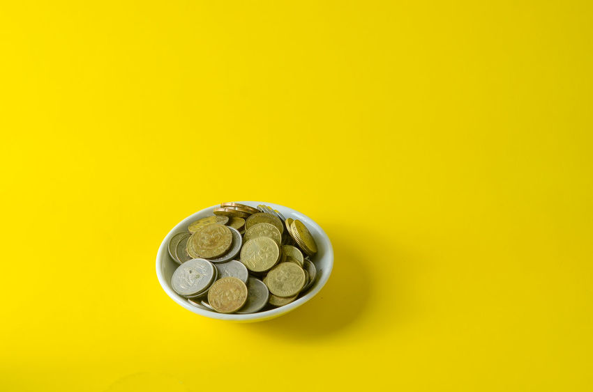 Abundance Business Coin Colored Background Copy Space Currency Cut Out Directly Above Economy Finance Indoors  Investment Large Group Of Objects Metal No People Savings Silver Colored Still Life Studio Shot Wealth Yellow Yellow Background