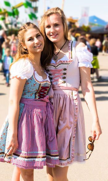 Portrait Of Smiling Young Female Friends Standing At Amusement Park