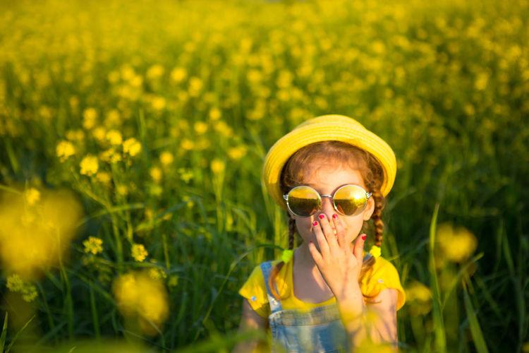 Portrait of man wearing yellow flower on field