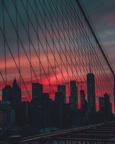 Silhouette of suspension bridge in city against sky during sunset