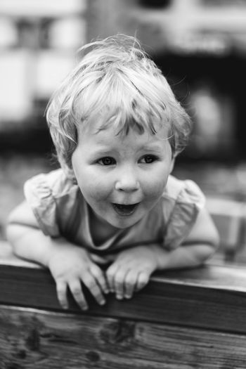Close-up of cute baby girl standing by railing