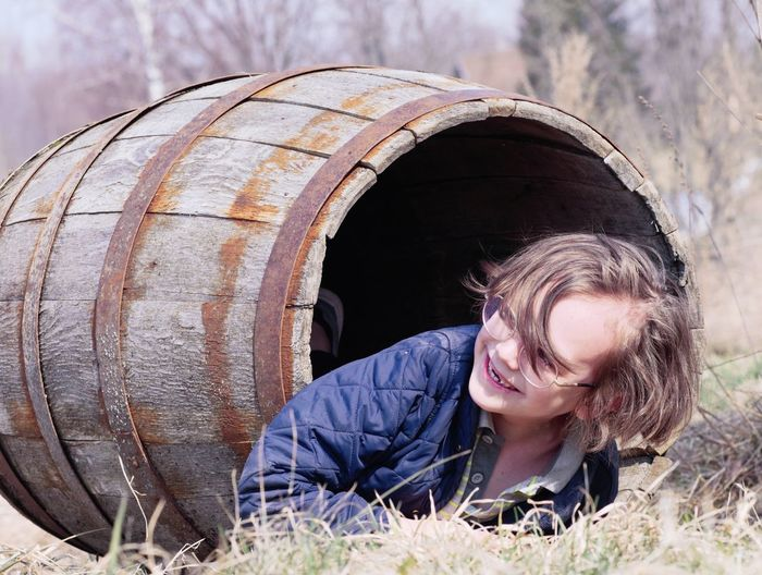Smiling boy looking away while lying in barrel over grass