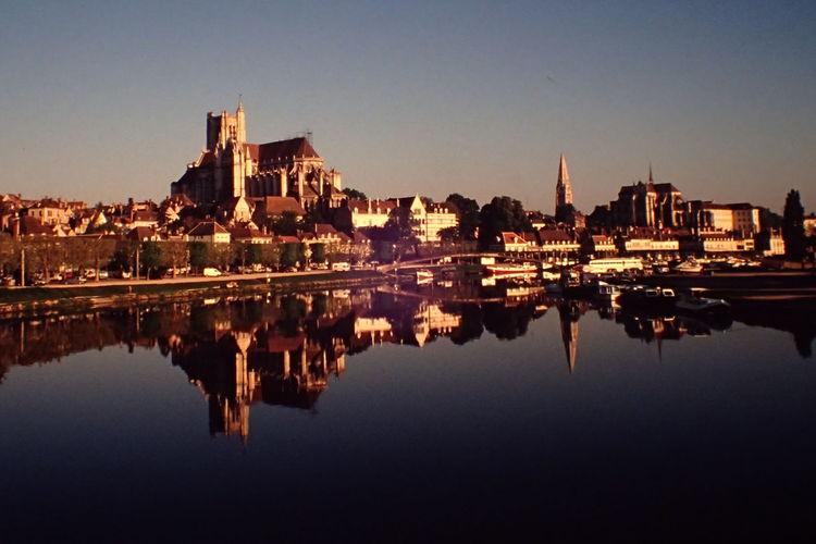 Reflection of illuminated cityscape against sky at night