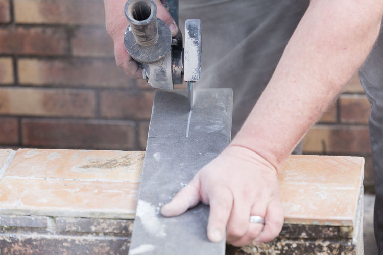 Midsection of man working with grinder