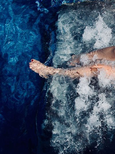 Low section of woman swimming in sea
