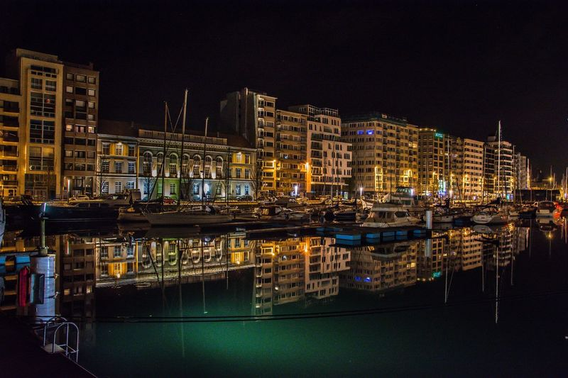 Illuminated boats moored at harbor against clear sky at night