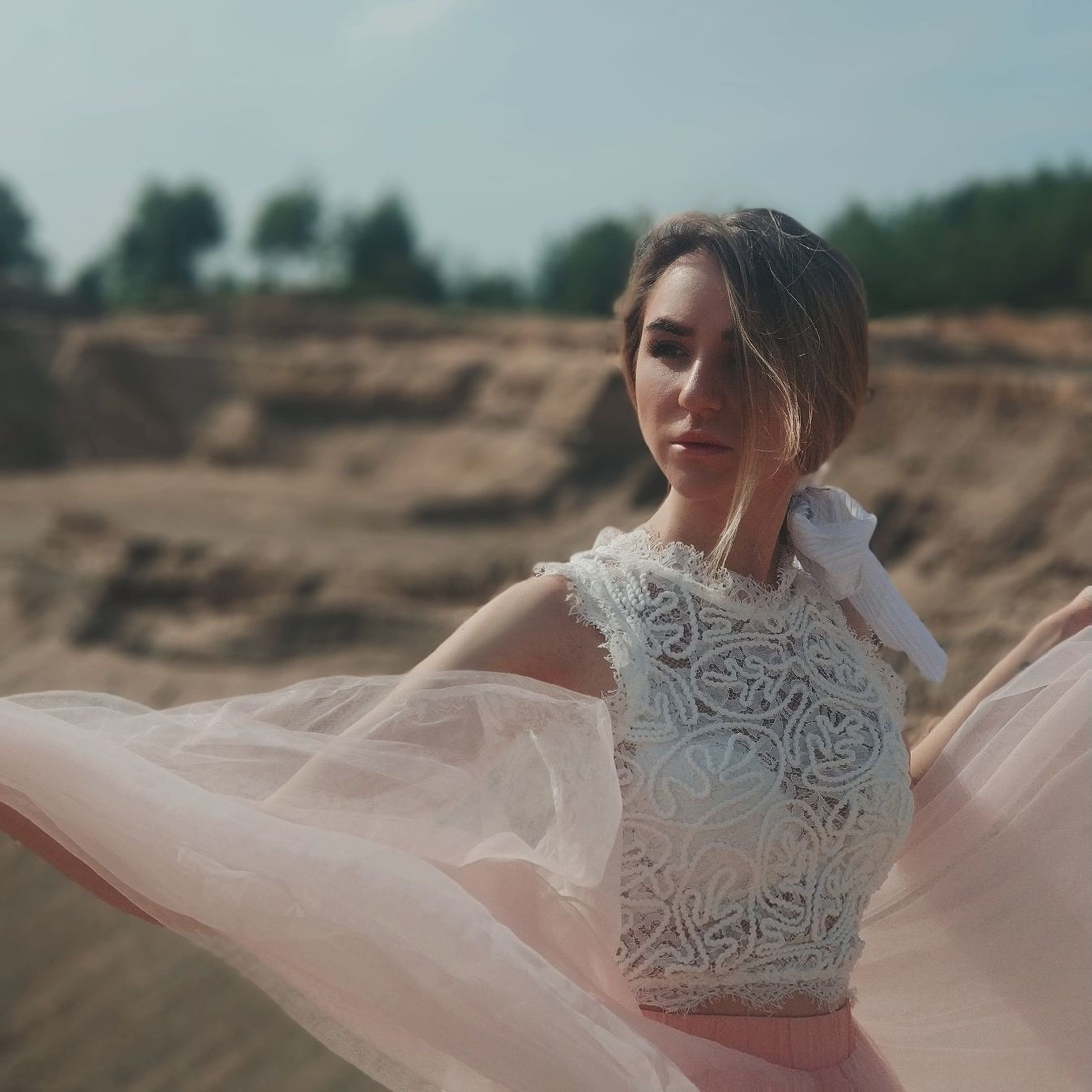 one person, young adult, beautiful woman, beauty, young women, real people, women, adult, leisure activity, lifestyles, land, focus on foreground, day, clothing, looking, sitting, nature, casual clothing, fashion, hairstyle, outdoors