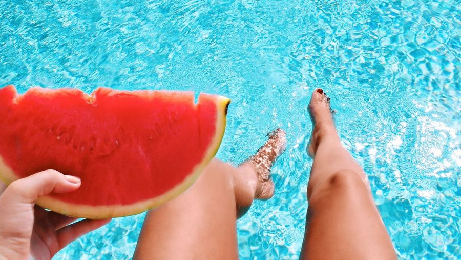 Low section of woman holding water melon in swimming pool