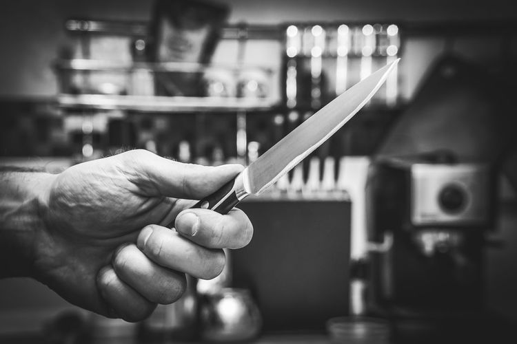 Cropped Hand Of Man Holding Knife In Kitchen