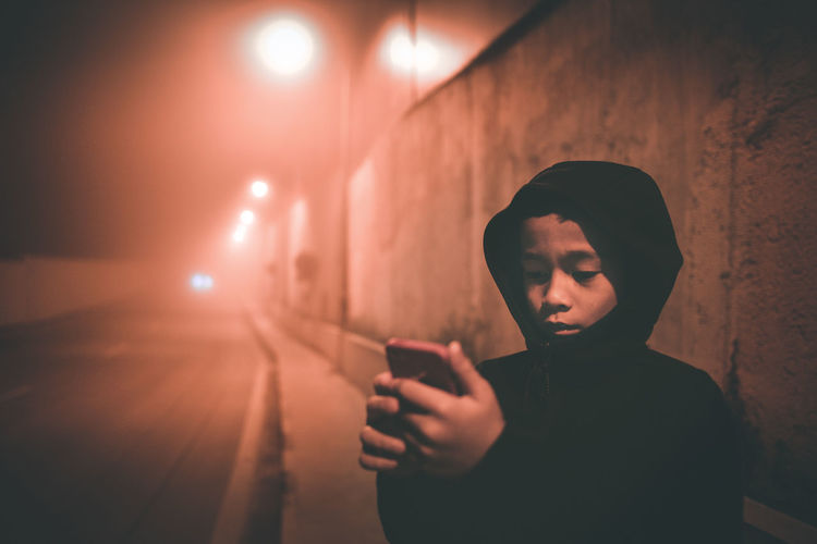 Boy Using Phone While Standing On Sidewalk At Night