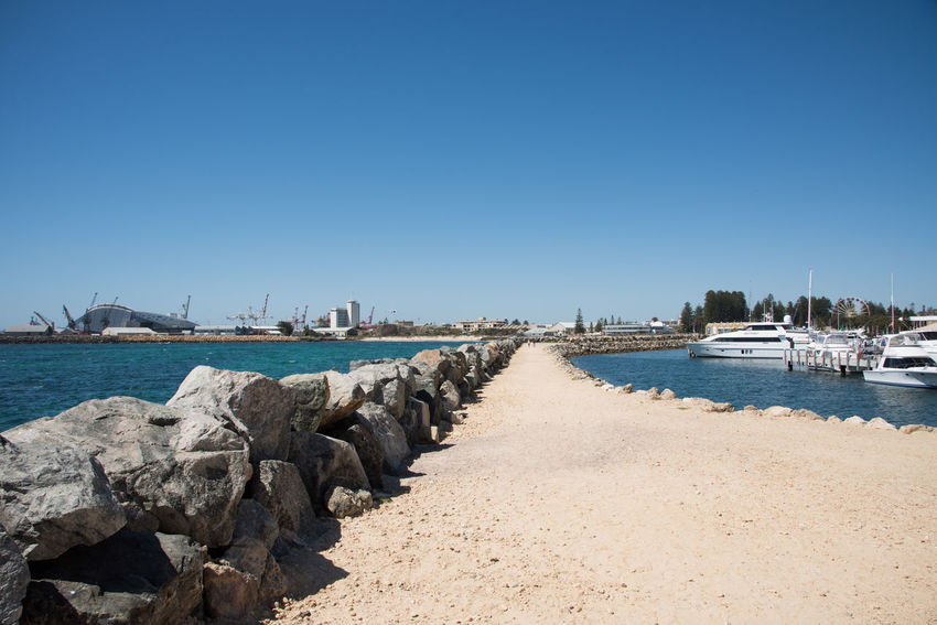 Footpath along rock groyne on the Indian Ocean coast with view of Royal Perth Yacht Club boat marina and the Maritime Museum in Fremantle, Western Australia. Architecture Beach Blue Building Exterior Clear Sky Footpath Fremantle  Groyne Harbor Maritime Museum Mode Of Transport Moored Nature Nautical Vessel Outdoors Rock - Object Royal Perth Yacht Club Sailboat Sea Sunlight Transportation Travel Destinations Water Western Australia Yacht