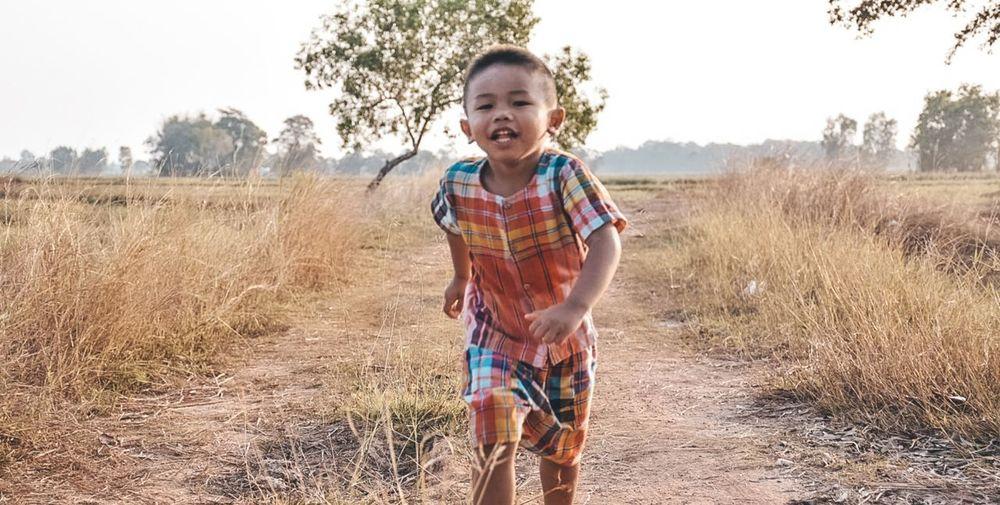 Portrait of happy boy standing on field