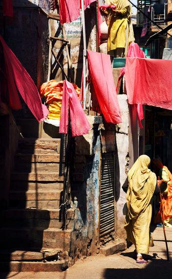Woman In Sari Walking Below Laundry Hanging Over Street In Town