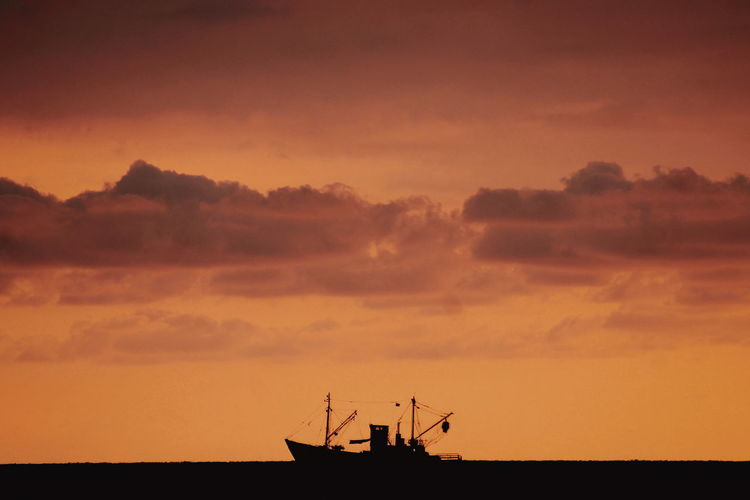 Silhouette boat in sea against cloudy sky during sunset