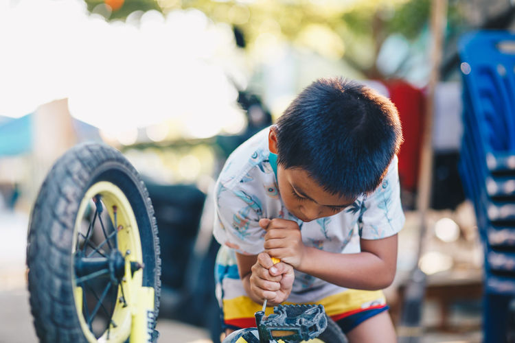 Boy repairing bicycle while standing outdoors