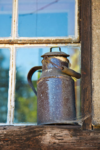 Milk can on a window. Churn Day Detail Focus On Foreground Historical Milk Can No People Old Weathered Window