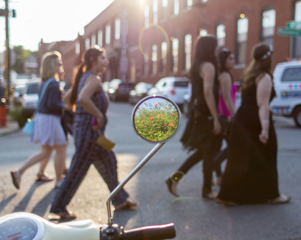 Women crossing street with flowers reflecting on rear-view mirror of motor scooter