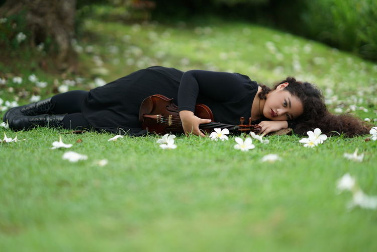Young Woman With Violin Lying On Grass