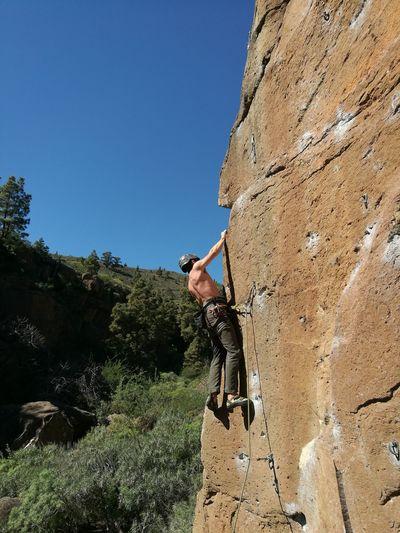 Low angle view of man climbing rock