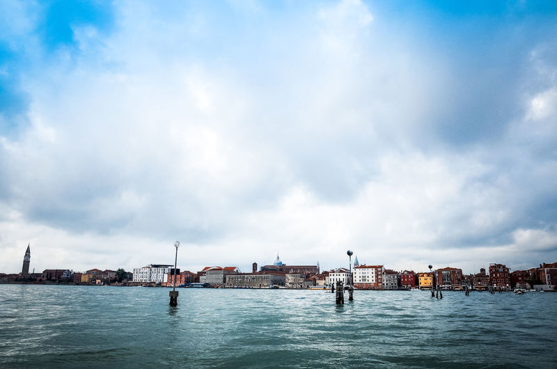 Grand canal by town against cloudy sky