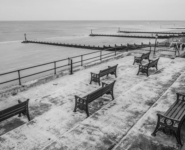 High Angle View Of Empty Benches By Sea