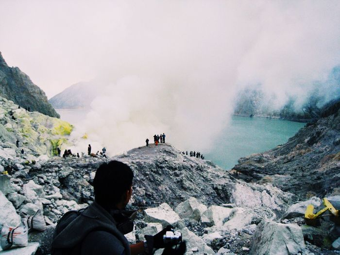 Rear view of man looking at tourists by ijen crater