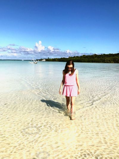 Young Woman Walking At Beach On Sunny Day