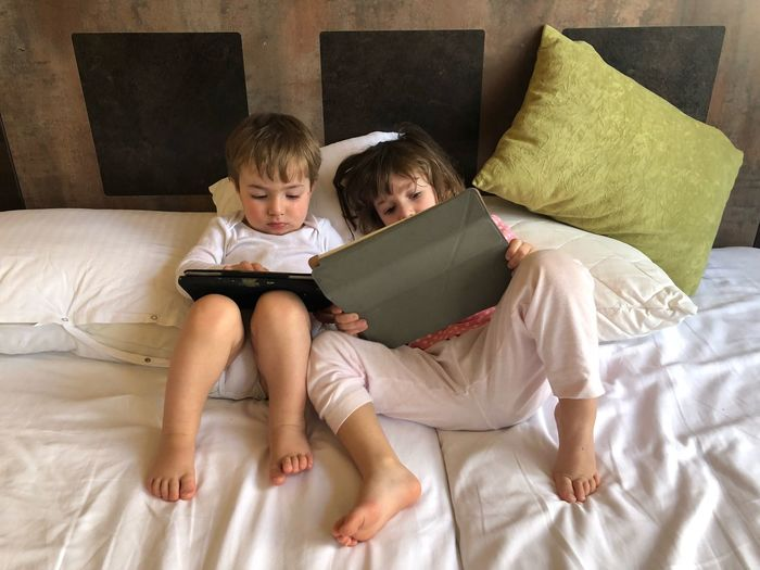 High Angle View Of Siblings Using Digital Tablet While Lying On Bed At Home
