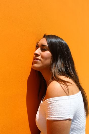 Young Woman With Closed Eyes Leaning On Orange Wall