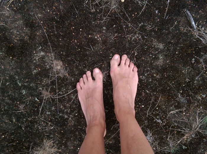 Person Standing Barefoot On Muddy Grounds