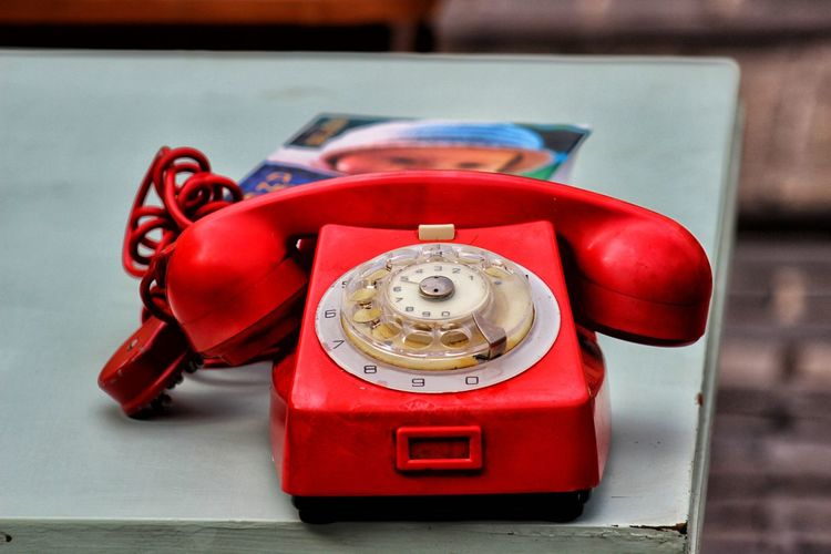 Close-up of red telephone on table