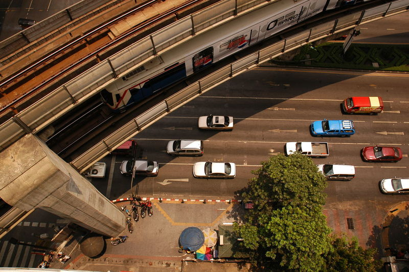 High Angle View Of Train On Bridge Over Cars Moving On Road
