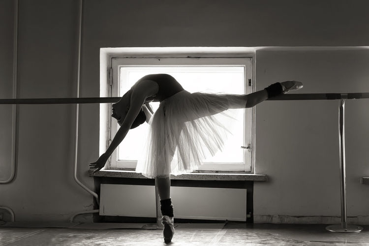 Full length of young ballet dancer balancing on floor