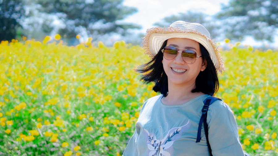 Portrait of smiling woman standing by yellow flowering plants
