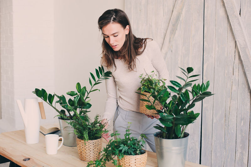 Young woman standing by potted plants on table at home
