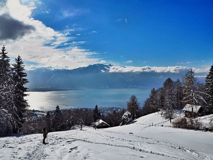 Scenic view of lake geneva and mountains during winter against blue sky