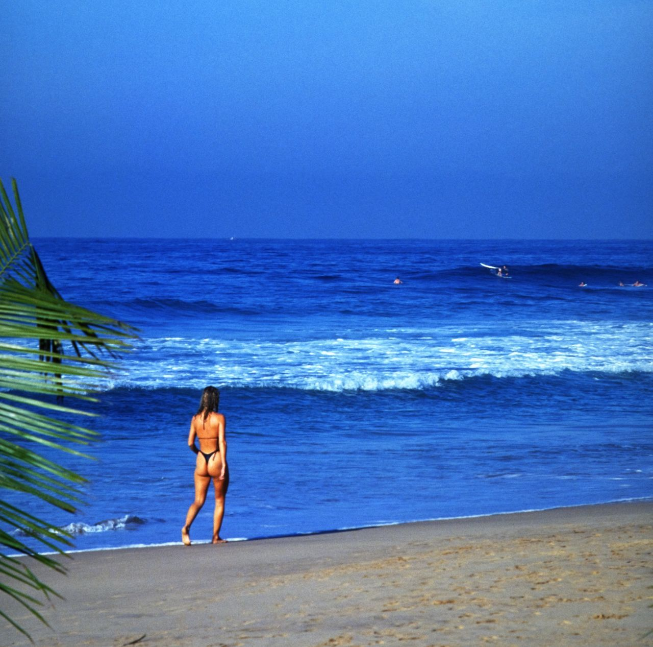 sea, horizon over water, water, beach, real people, nature, scenics, beauty in nature, full length, shirtless, sky, one person, lifestyles, walking, leisure activity, standing, outdoors, blue, sand, men, vacations, wave, clear sky, day, young adult, people