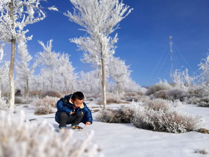 Little boy crouching on snow covered field